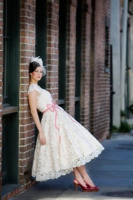 Koronkowa sukienka ślubna w stylu lat 50-tych z ozdobną różową kokardą (źródło: pinterest.com)