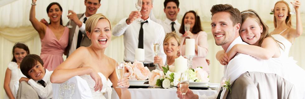 przyjęcie weselne, zdjęcie uśmiechniętej młodej pary przy stole z przyjaciółmi i rodziną na