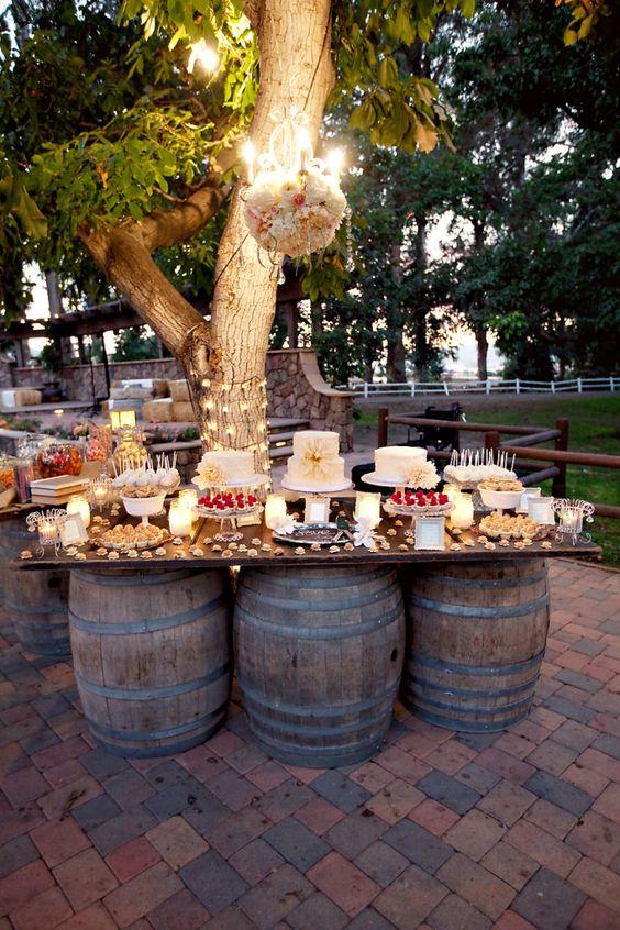 wesele w stylu rustykalnym - stół w plenerze w formie płyty ustawionej na trzech beczkach pod drzewem z podwieszonym pięknie udekorowanym żyrandolem
