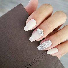 ślubny manicure w mlecznym kolorze z dekoracją z cyrkonii na paznokciu palca serdecznego i u podstawy paznokcia pa;ca środkowe
