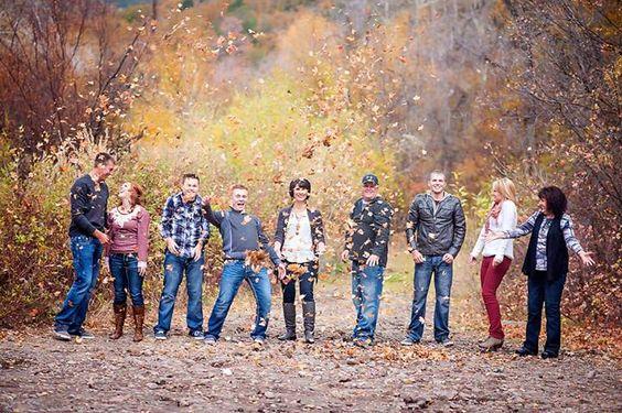 fotografia rodzinna poznań - grupa ludzi pozuje do zdjęcia w jesiennej oprawie rzucając liśćmi