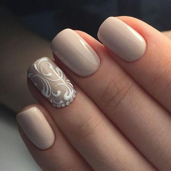 ślubny manicure w kolorze beżowym z przepięknym biały ażurem na paznokciu palca serdecznego
