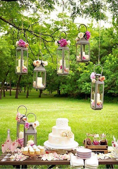 wesele w stylu rustykalnym i dekoracje stołu w tym stylu - lampiony podwieszane i stół ustawiony na świeżym powietrzu udekorowany stroikami z kwiatów w kolorze różu i kremu
