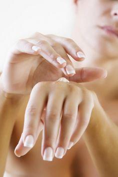 domowe manicure - na pierwszym planie piękne i zadbane dłonie z pięknymi paznokciami na które młoda kobieta nakłada krem