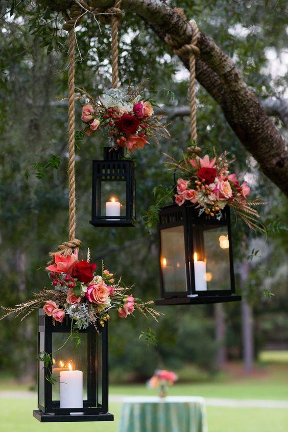 wesele w stylu rustykalnym to również przepiękne dekoracje np. lampiony podwieszone na linie na gałęzi i przybrane stroikami kwiatowymi