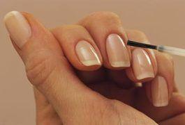 domowe manicure - nakładanie pędzelkiem bezbarwnego olejku zmiękczającego na skórki