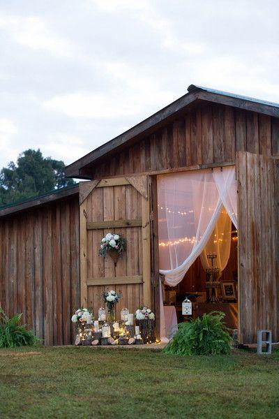wesele w stylu rustykalnym - romantycznie udekorowane wejście do stodoły kwiatami i materiałem