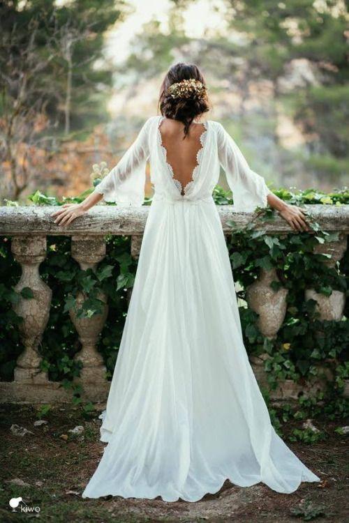 piękna zwiewna z odkrytymi plecami suknia ślubna w stylu boho na modelce z upiętymi włosami udekorowanymi kwiatami stojącej przy kamiennej balustradzie obrośniętej winoroślami
