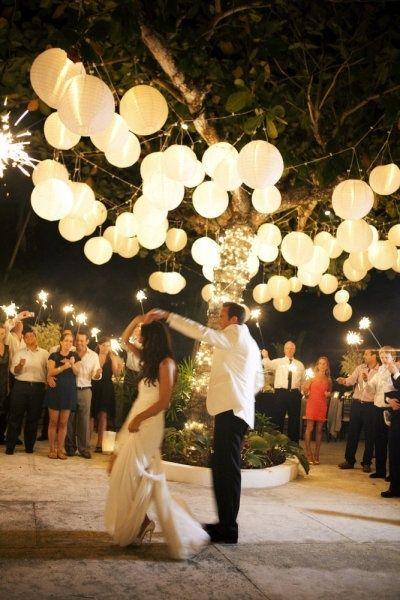 wesele pod gołym niebem pełne światła dzięki podwiesonym lampionom i zimnym ogniom trzymanych przez goźci podczas pierwszego tańca państwa młodych