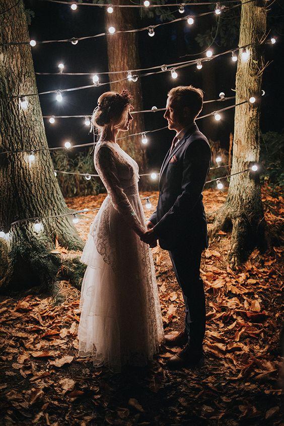 młoda para trzyma się za ręce w romantycznym stylu boho gdzie w tle sąi rozwieszonemiędzy drzewami światełka