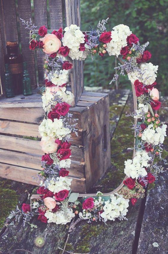 duża drewniana litera D udekorowana czerwonymi i białymi kwiatami na tle drewnianych skrzynek