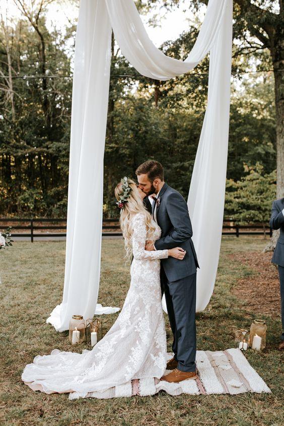 całująca się młoda para na ślubie w stylu boho na świeżym powietrzu