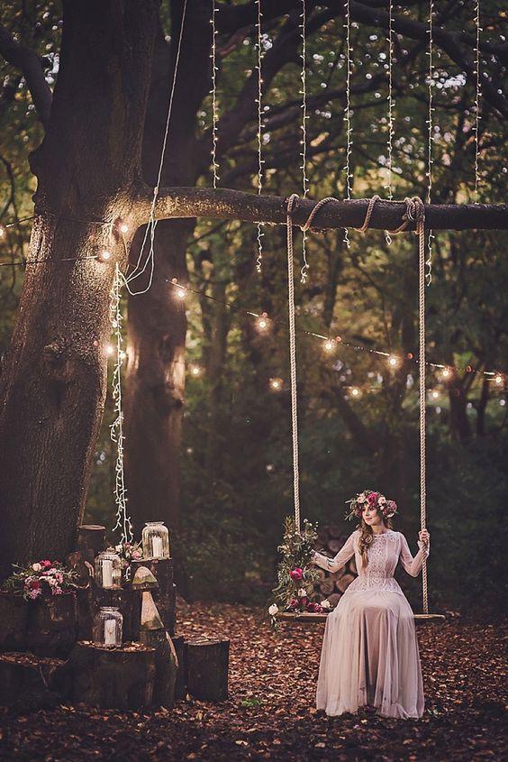 fotografia panny młodej w stylu boho siedzącej na huśtawce zamontowanej na gałęzi drzewa do której podczepione zostały światełka
