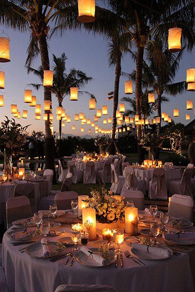 wesele pod palmami, stoliki oświetlone dużą ilością lampionów rozwieszonych pomiędzy nimi