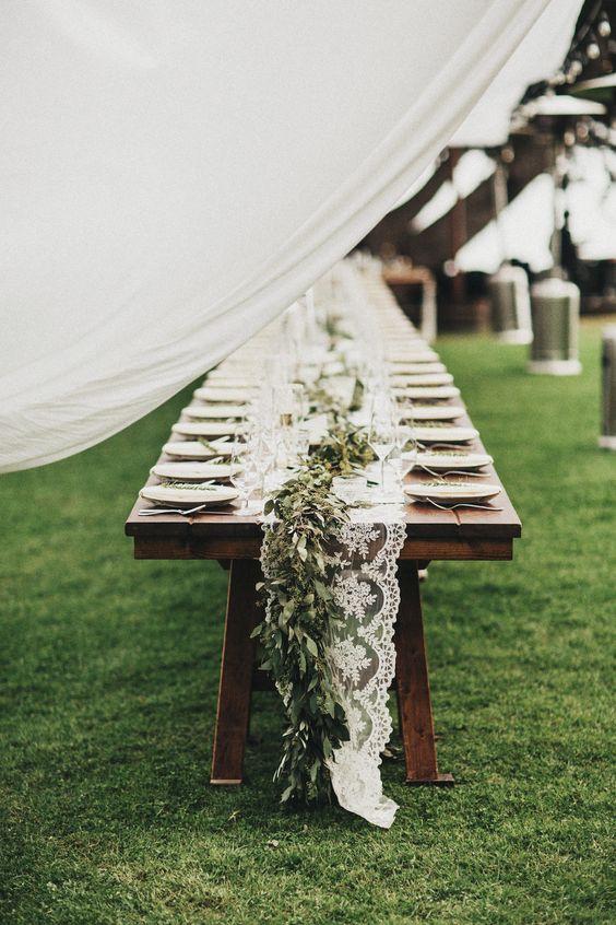 dekoracja stołu weselnego stylu boho, drewniana długa ława z koronkowym bieżnikiem udekorowana świeżymi roślinami