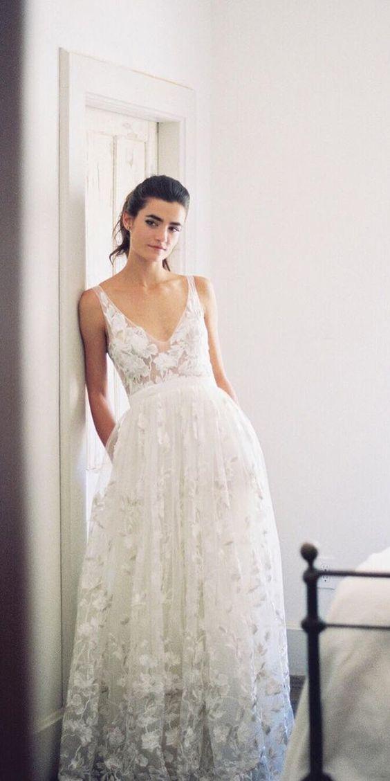 panna młoda w koronkowej sukni na ramiączkach w stylu boho oparta o białą framugę drewnianych drzwii
