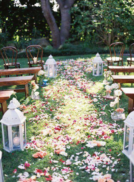 miejsce ślubu w stylu boho - ceremonia na świeżym powietrzu z drewnianymi ławami i udekorowane płatkami kwiatów i lampionami