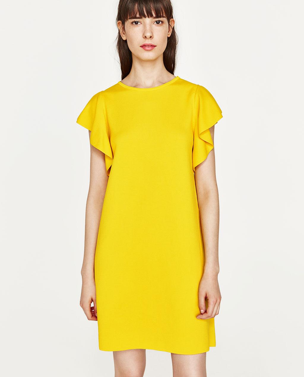 żółta minimalistyczna do połowy uda sukienka na wesele z falbaniastymi rękawkami